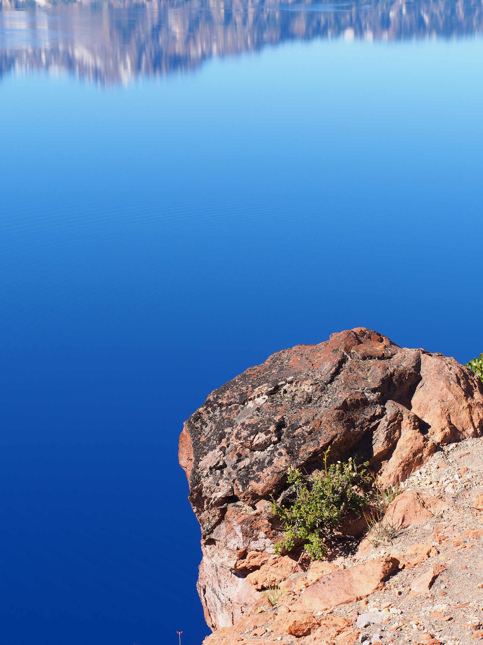 A jagged cliff over a brilliant blue Crater Lake in Southern Oregon on a beautiful summer morning.
