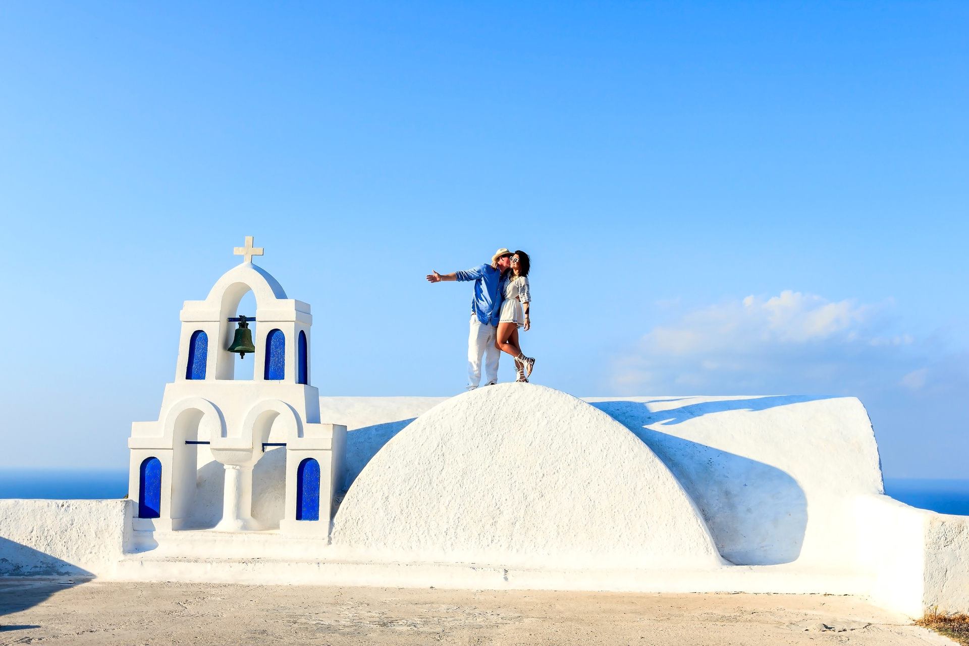 Couple enjoying city. Couple enjoying posing on chapel with beautiful blue sky on background in Santorini, Greece
