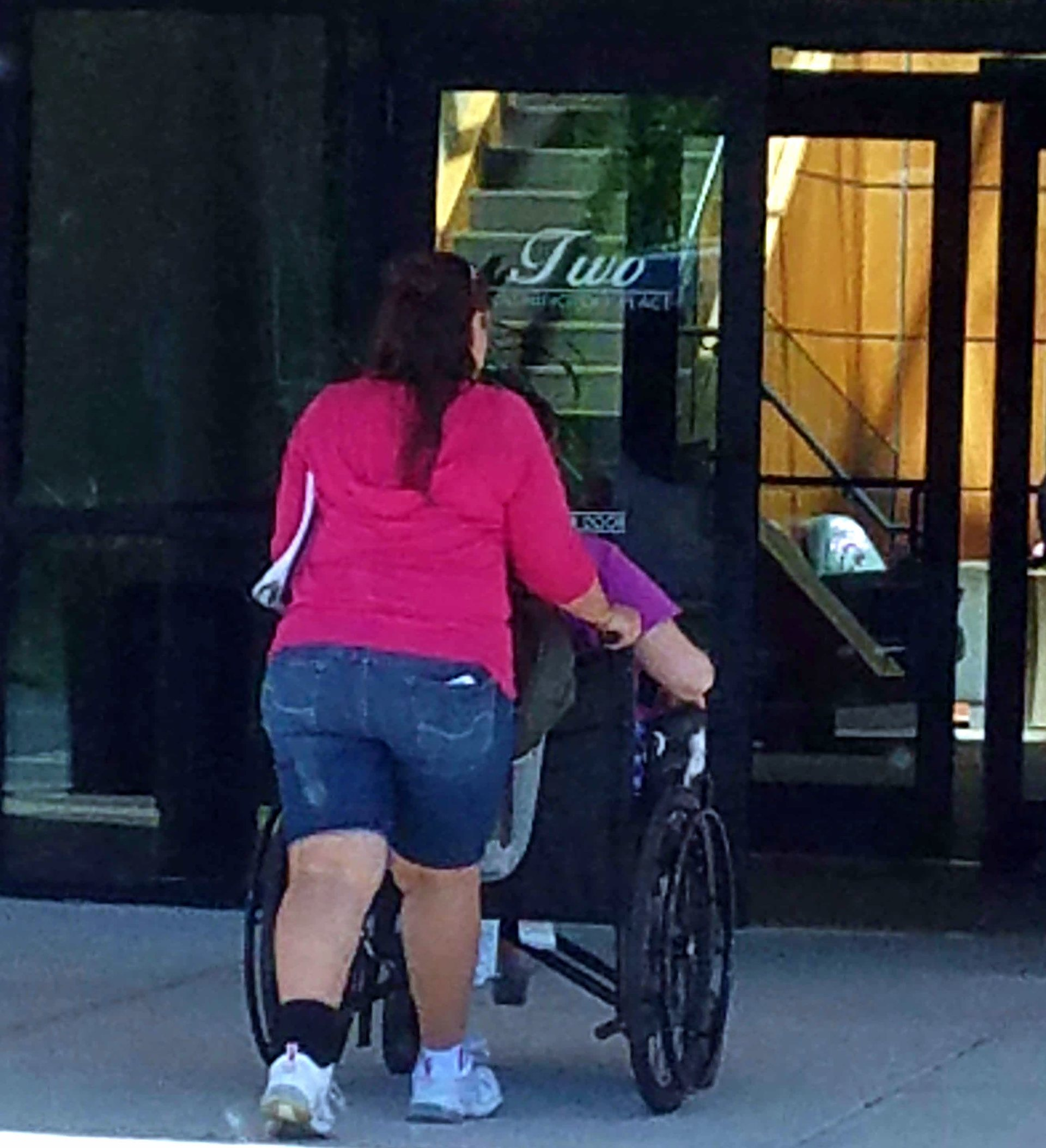 Pushing person in wheelchair into building.