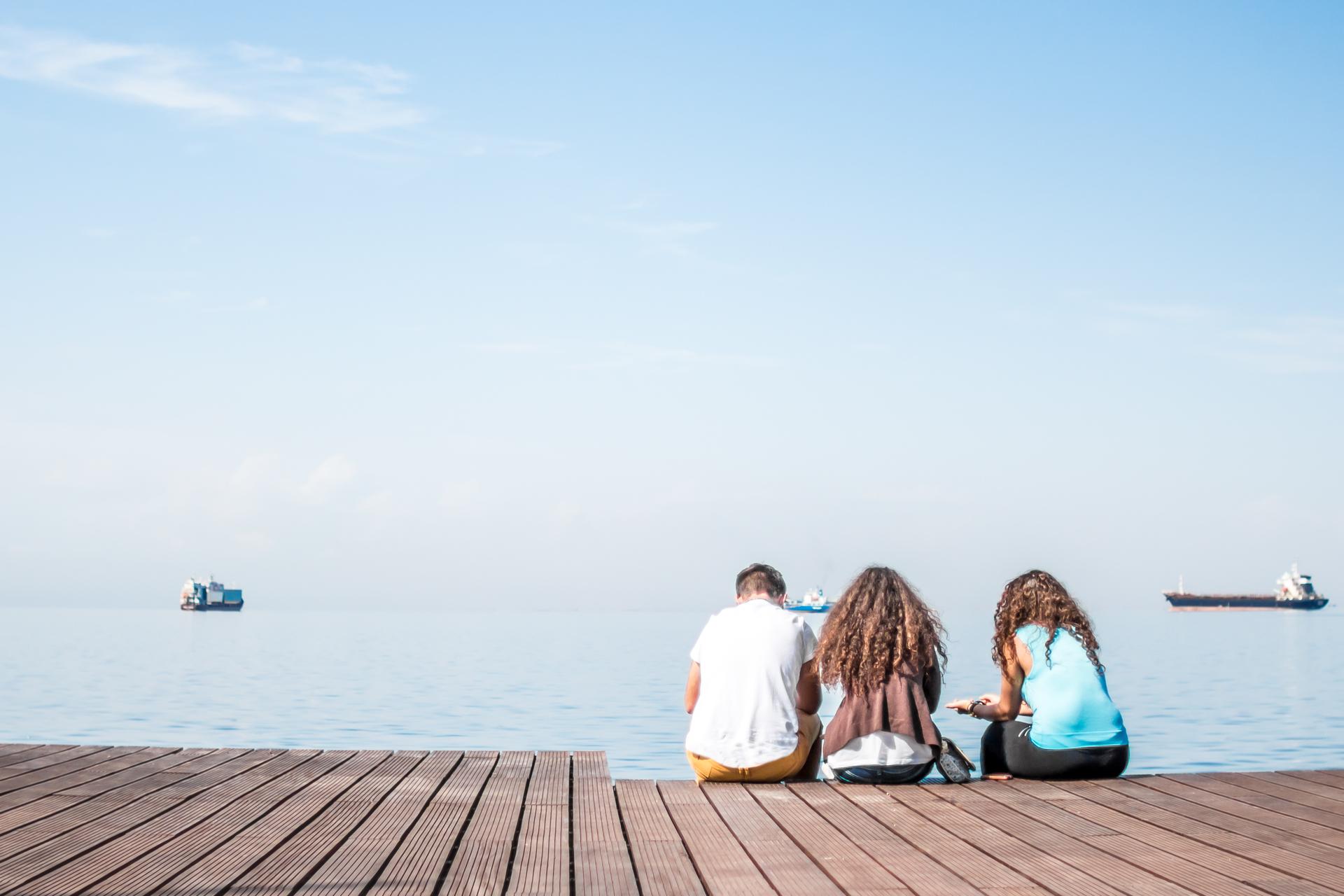 Friends Sitting On Wooden Dock